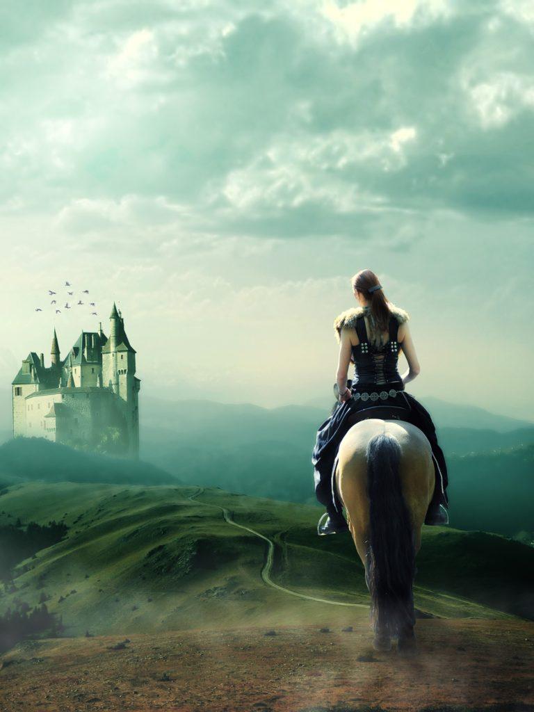 Eine Frau auf einem Pferd reitet auf ein Schloss zu. Sie trägt ein Mieder und, wenn man genau hinsieht, vermutlich nichts drunter. Ist das schon Sexismus?